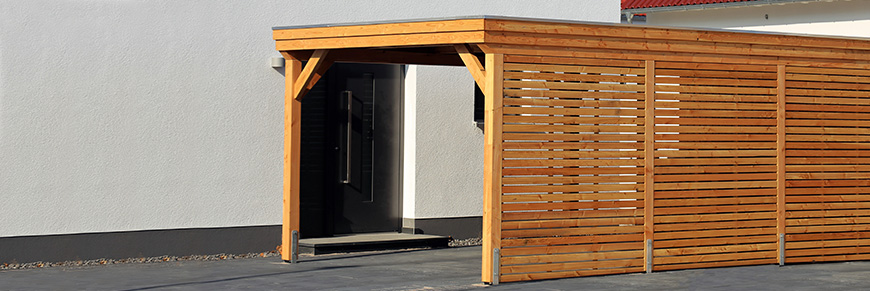 Carport aus Holz vor einem weißen Haus