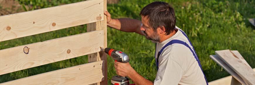 Mann befestigt einen Lattenzaun